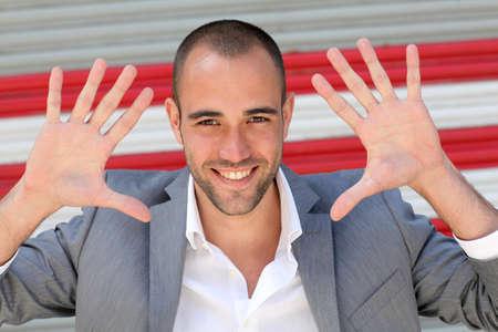 кавказцы: Привлекательный мужчина показывает рукой ладони к камере