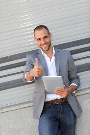 Man leaning on wall with electronic tablet photo
