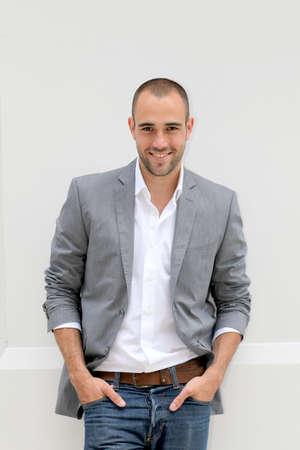 Handsome smiling man leaning on wall Reklamní fotografie