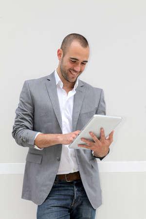 iş adamı: Beyaz zemin üzerine elektronik tablet kullanarak cool işadamı
