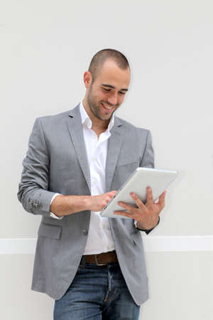 cheerful businessman: Cool businessman using electronic tablet on white background Stock Photo