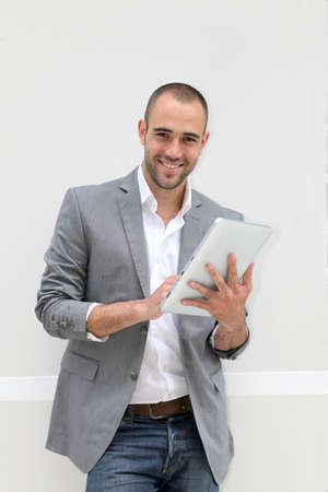 modern businessman: Cool businessman using electronic tablet on white background Stock Photo