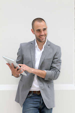 Cool businessman using electronic tablet on white background photo