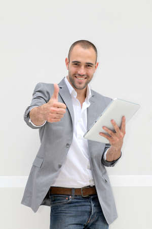 Cheerful young man showing thum up Stock Photo - 10814997