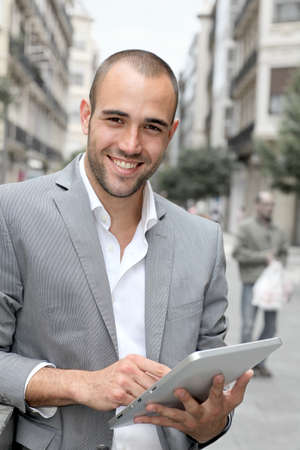 cheerful businessman: Man with suit jacket using touchpad in town Stock Photo