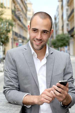 magabiztos: Nyugodt üzletember, mobiltelefonnal a városban