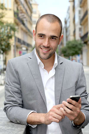 Relaxed businessman with mobile phone in town Stock Photo - 10013450