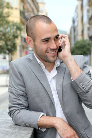 telephone salesman: Relaxed businessman with mobile phone in town Stock Photo