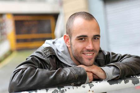 chaqueta de cuero: Hombre sonriente joven con chaqueta de cuero en la ciudad Foto de archivo
