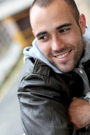 Smiling young man with leather jacket in town photo