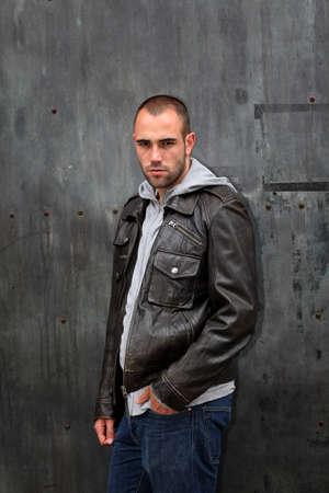 Man with leather jacket standing on metal door photo