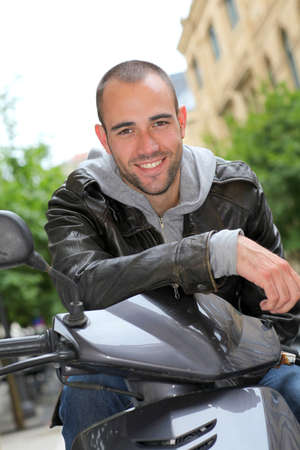 Portrait of young man sitting on motorcycle in town photo
