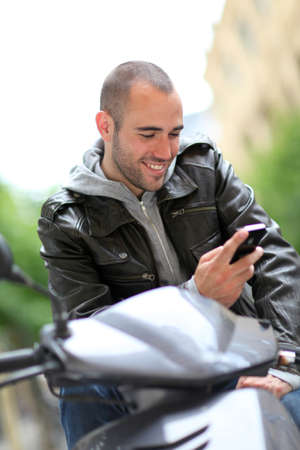 Young man sitting in motorcycle with telephone photo