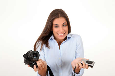 reflex: Young woman comparing digital compact and reflex cameras Stock Photo