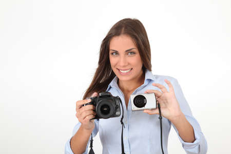 Young woman comparing digital compact and reflex cameras Stock Photo - 10284280