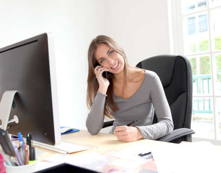 secretary woman: Portrait of beautiful office worker sitting at her desk