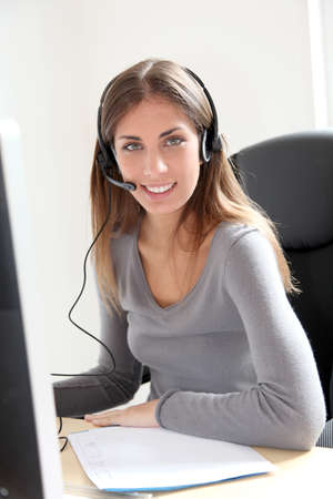 telephone saleswoman: Portrait of beautiful office worker sitting at her desk
