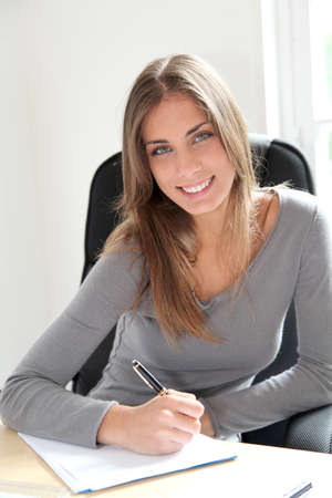 noting: Portrait of beautiful office worker sitting at her desk