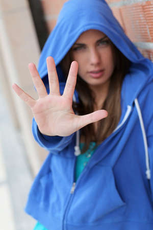 rebel: Teenager with blue sweater showing hand to camera