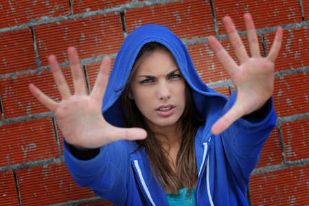 Teenager with blue sweater showing hand to camera photo
