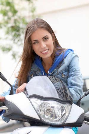 vespa: Mujer joven sentada en moto fuera