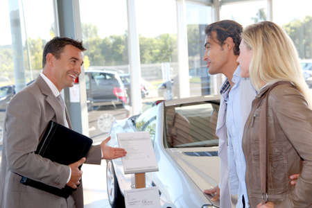 Car seller with couple in car dealership Stockfoto