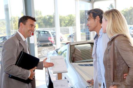 Vendeur de voiture avec couple au concessionnaire automobile Banque d'images