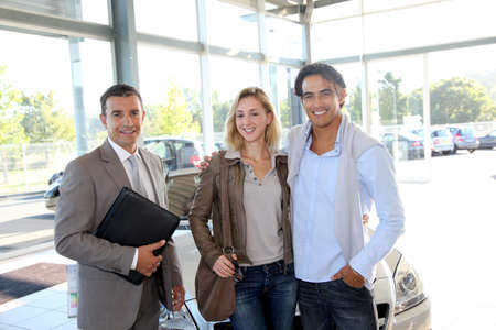 automobile dealers: Car seller with couple in car dealership Stock Photo