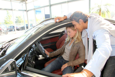 Couple looking inside new car photo