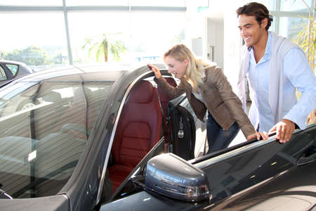 purchasers: Couple looking inside new car