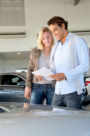 purchasers: Couple reading car documentation in showroom