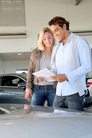 estimate: Couple reading car documentation in showroom