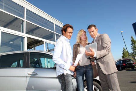 car showroom: Car seller with couple looking at electronic tablet