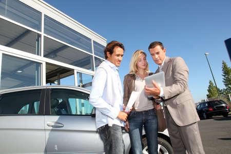vendeurs: Vendeur de voiture avec couple regardant tablette �lectronique