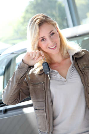 Smiling woman holding brand new car key photo