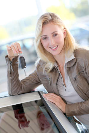 purchaser: Smiling woman holding brand new car key