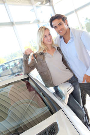 purchasers: Happy couple holding new car keys