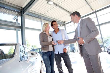 car showroom: Car seller giving keys to new car owners