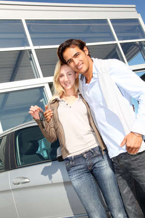 Couple holding car key in automobile dealership photo