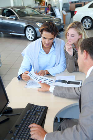 automobile dealers: Car seller and couple looking at catalogue Stock Photo