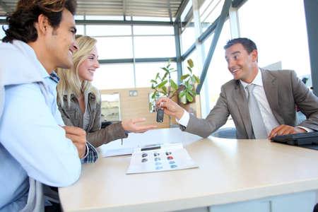 showroom: Car seller giving car key to buyers