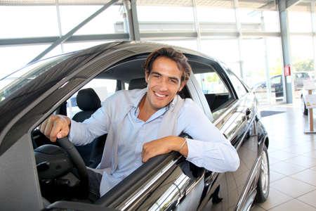 rental: Hombre sonriente sentado en el volante del coche nuevo