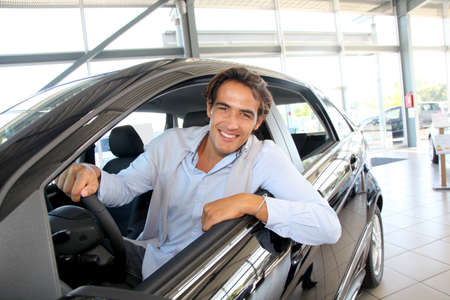 rental car: Smiling man sitting at the steering-wheel of brand new car
