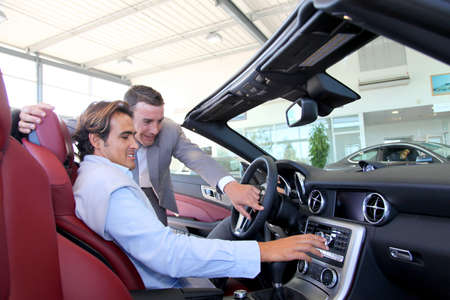 automobile dealers: Car seller showing interior details to purchaser
