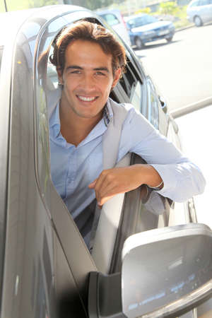Smiling man sitting at the steering-wheel of brand new car photo