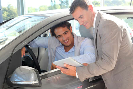 Car seller with car buyer looking at electronic tablet photo