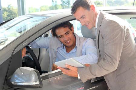 Le vendeur de voiture avec acheteur de voiture regardant tablette électronique