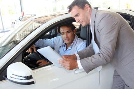 car dealer: Car seller with car buyer looking at electronic tablet Stock Photo