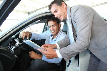 Car seller with car buyer looking at electronic tablet Stock Photo - 10624886