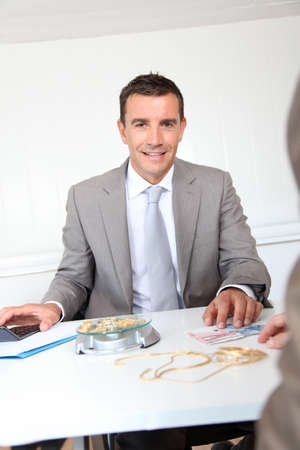 Businessman paying for golden jewels photo